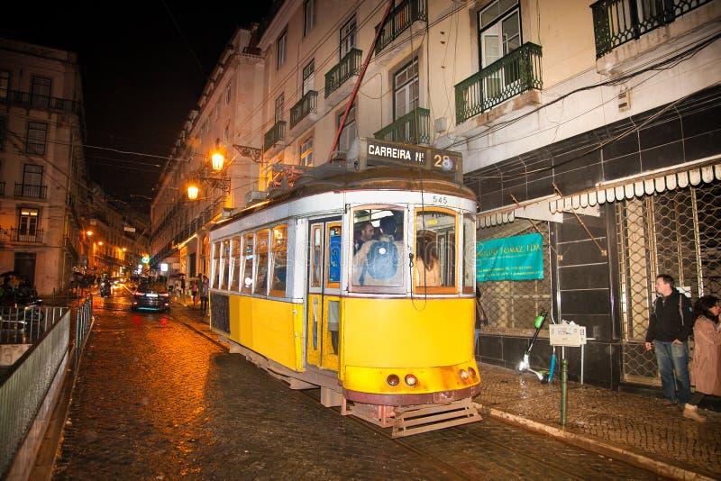 Berömd spårvagn för tappningguling 28 av av Alfama, i det äldsta området av den gamla staden, på natten, Lissabon, Portugal arkivbilder
