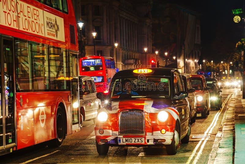 Berömd taxitaxi på en gata i London arkivfoto