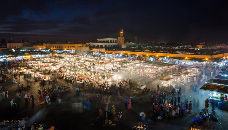 Berömda fyrkantiga Jemaa El Fna som är upptagen med många personer och ljus under natten, medina av Marrakesh, Marocko arkivbilder