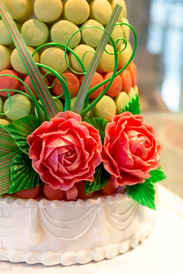 Berömkaka med macarons och sockerrosor royaltyfria bilder