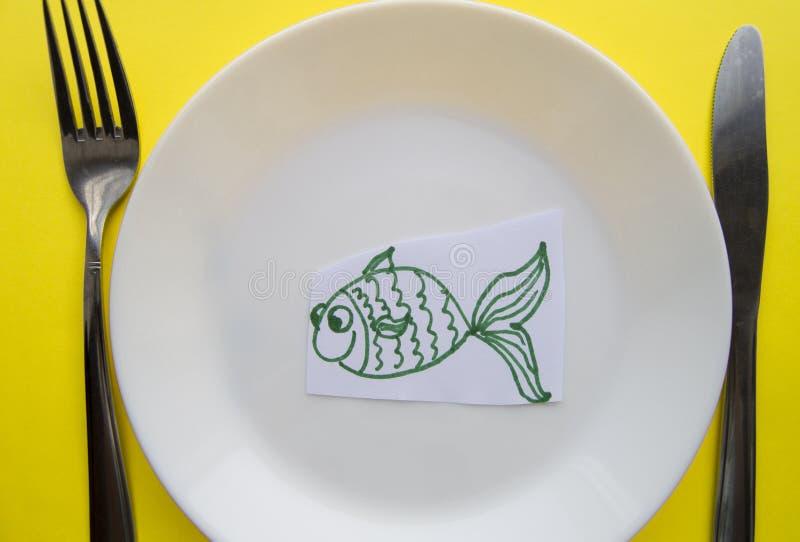 Berömmen av April dumboms dag, en platta med en gaffel och kniv och en pappers- fisk på en gul kulör bakgrund blidka arkivfoton
