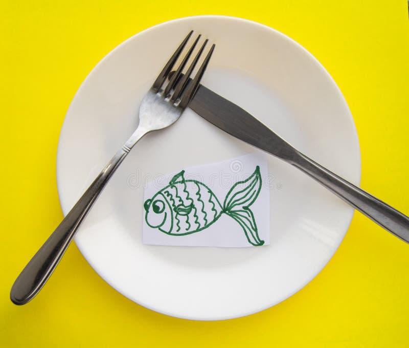 Berömmen av April dumboms dag, en platta med en gaffel och kniv och en pappers- fisk på en gul kulör bakgrund blidka arkivbild