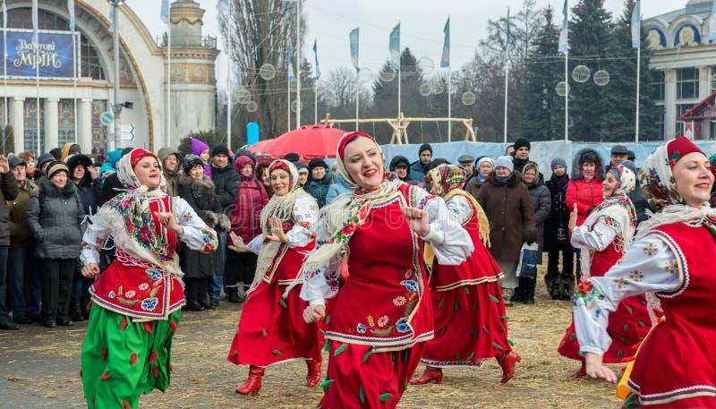 Berömmen av Maslenitsaen Shrovetide i staden Traditionella danser av iklädda folk dräkter för kvinnor royaltyfri bild