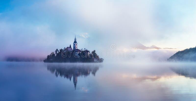 Berühmte Insel mit alter Kirche in der Stadt von Bled Nebelhafter Morgen lizenzfreies stockfoto