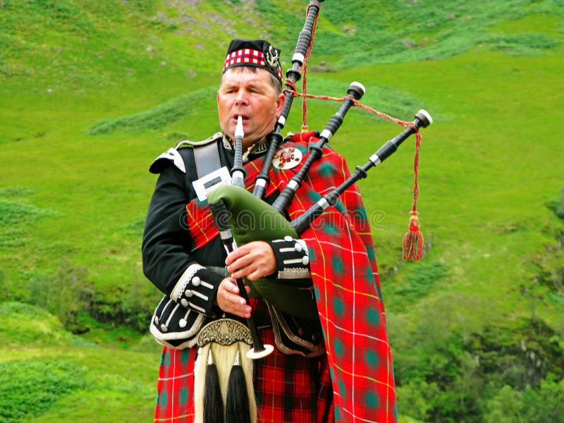 Berühmter Dudelsackmusiker, der traditionelle Kleidung trägt stockfotografie