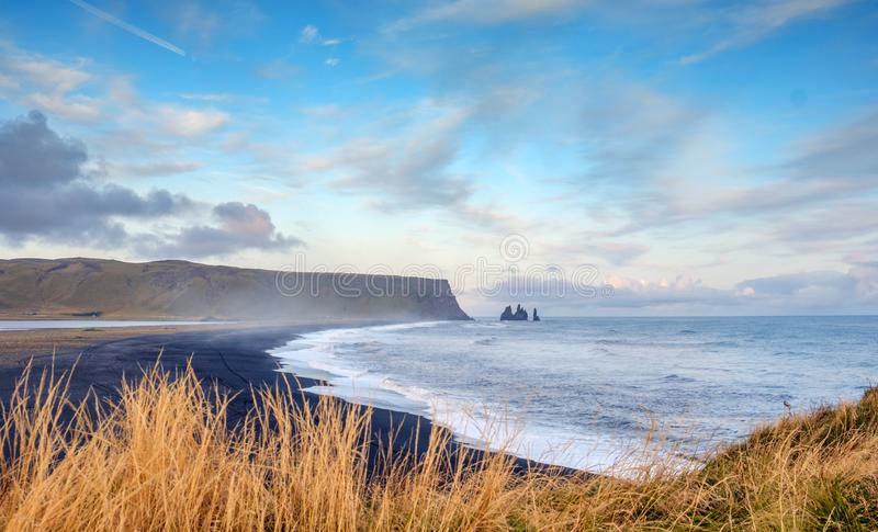 Berühmter Schwarzer Sandstrand Reynisfjara in Island, windiger Morgen, Meereswaves, farbenfrohe Sky lizenzfreies stockfoto