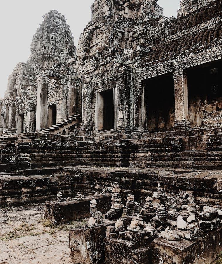 ber?mda forntida sned framsidor f?r angkorbayon cambodia dess khmer sk?rdar fridfull sikt f?r vertical f?r torn f?r siemtempeltho arkivfoton