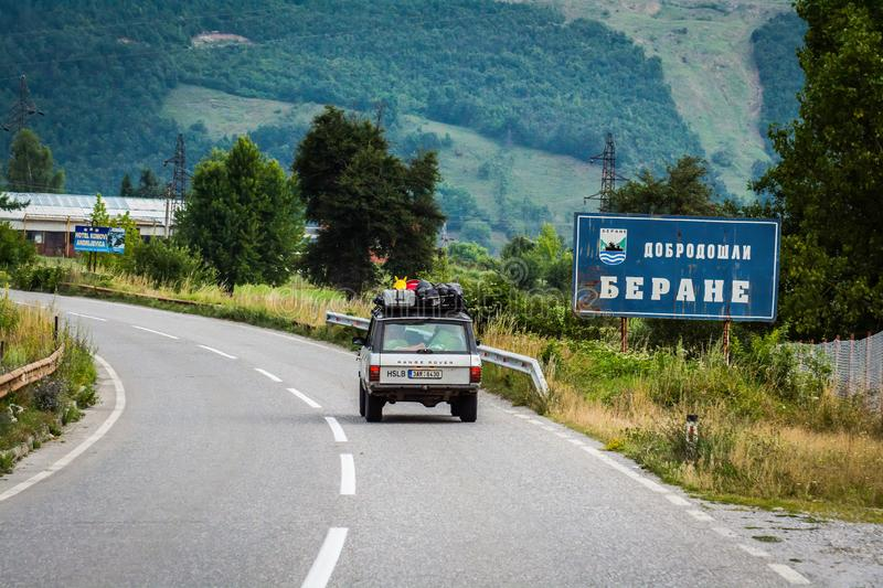Berane, Montenegro - July 21, 2014. Vintage off road car passing by signboard in native serbian language Welcome to Berane.  royalty free stock images