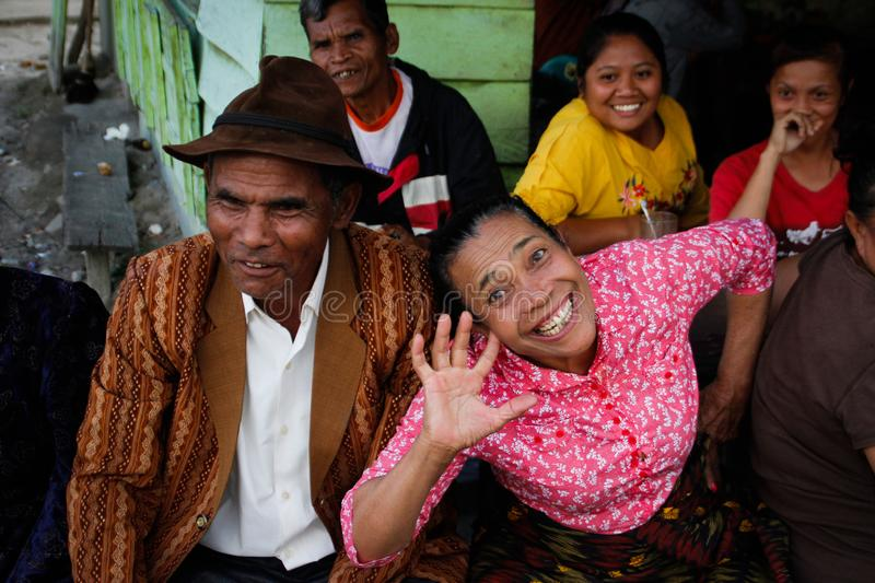 Very cheerful laughing and fumbling Indonesian elderly woman in a pink blouse and her stylishly dressed man in a brown hat royalty free stock images