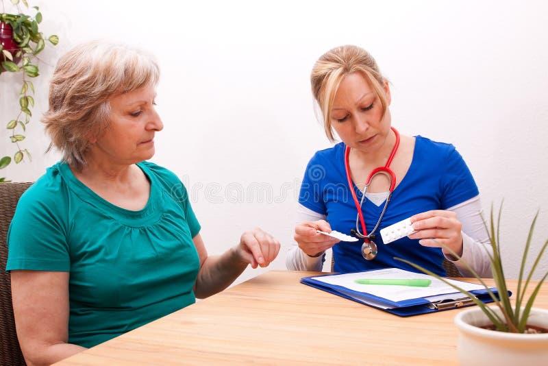 Beraten eines Seniors auf der Dosis der Medikation lizenzfreies stockfoto