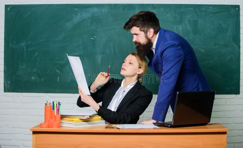 Beraten Sie sich mit Kollegen Helfen Sie mir mit Dokumenten Lehrer und Aufsichtskraft, die im Schulklassenzimmer zusammenarbeiten stockfotos