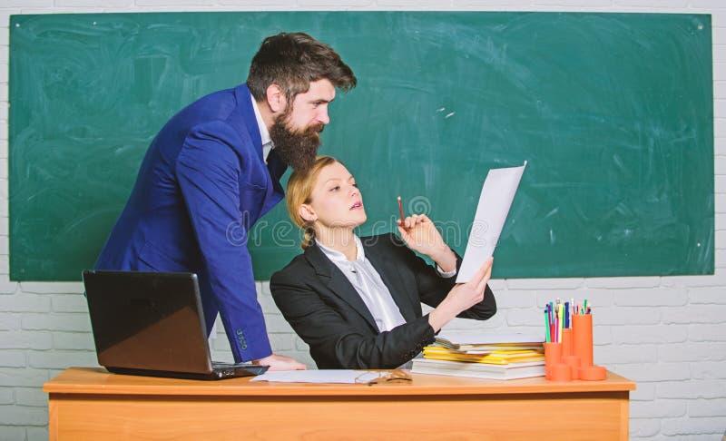 Beraten Sie sich mit Kollegen Helfen Sie mir mit Dokumenten Lehrer und Aufsichtskraft, die im Schulklassenzimmer zusammenarbeiten lizenzfreies stockbild