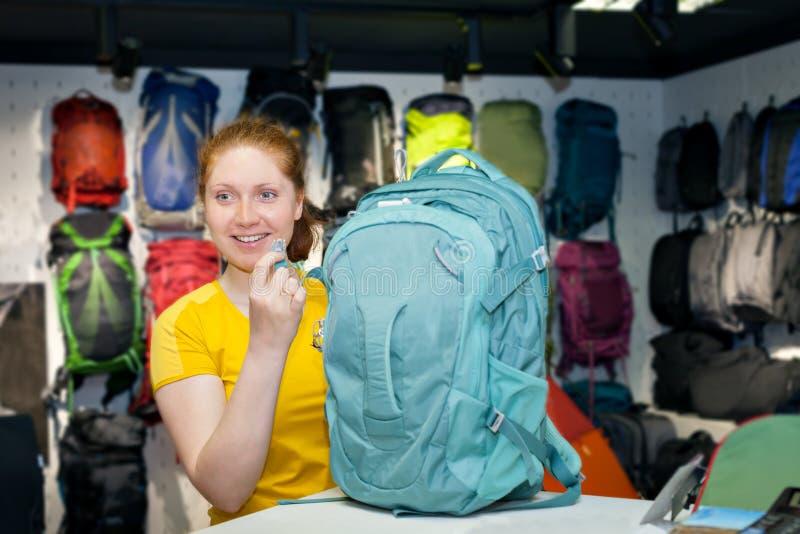 Berater des jungen Mädchens in einem Facheinzelhändler für den Tourismus wählt Rucksack aus stockbilder