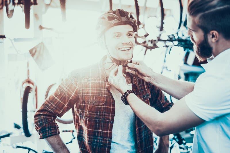 Berater Helps Guy Try auf Sturzhelm für Fahrrad-Fahrten lizenzfreie stockfotografie
