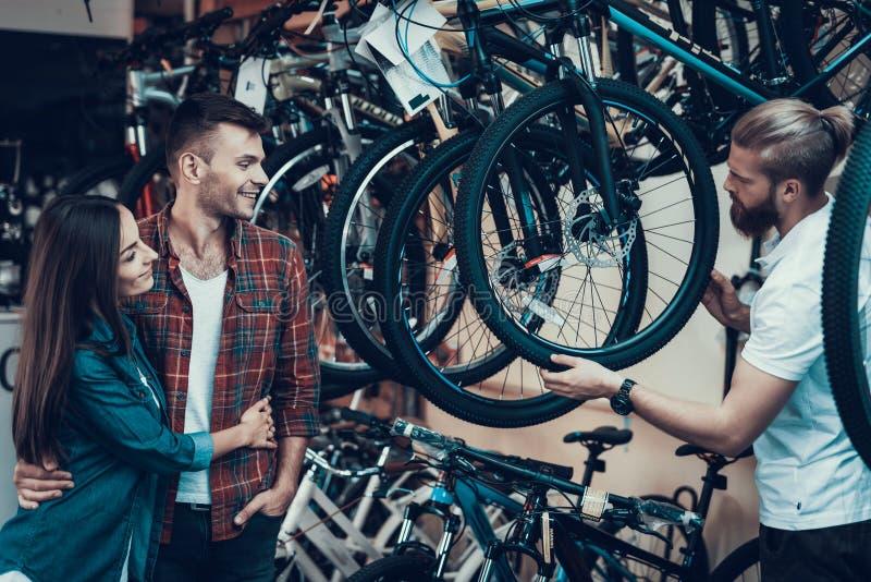 Berater Helps Young Couple beim Fahrrad-Wählen lizenzfreie stockfotografie