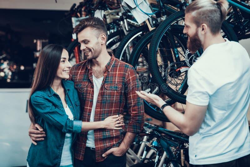 Berater Helps Young Couple beim Fahrrad-Wählen stockbilder