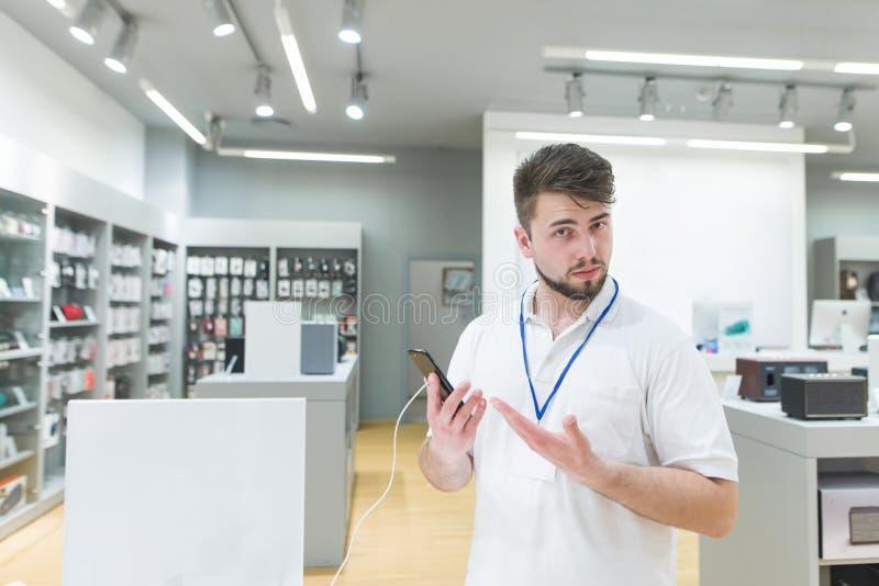 Berater ist im Elektronikladen und empfiehlt den Smartphone in seinen Händen stockfotos