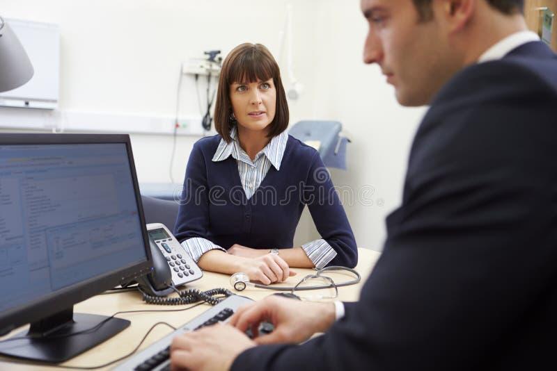 Berater Meeting With Patient im Büro lizenzfreie stockfotografie