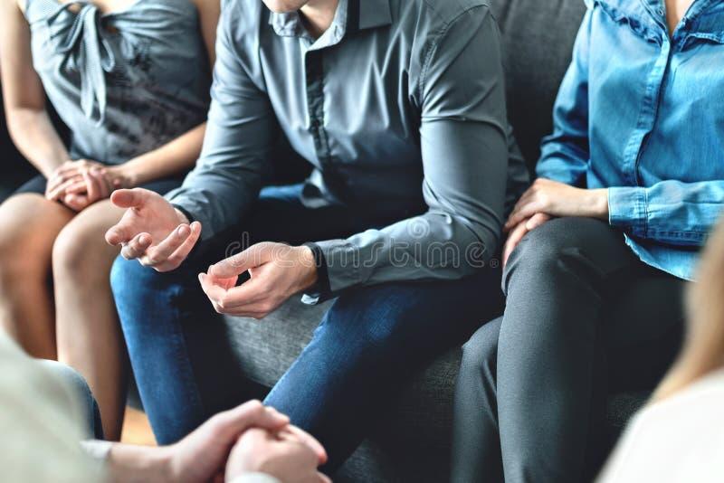 Beratung und Gespräch in der Gruppentherapie oder -sitzung Mann, der Geschichte zur Gemeinschaft teilt Zuf?llige Gesch?ftsleute i stockfotografie