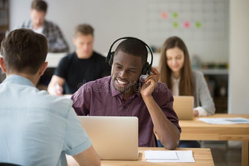 Beratungskunde des Afroamerikaners, der drahtlosen Kopfhörer verwendet lizenzfreie stockfotos