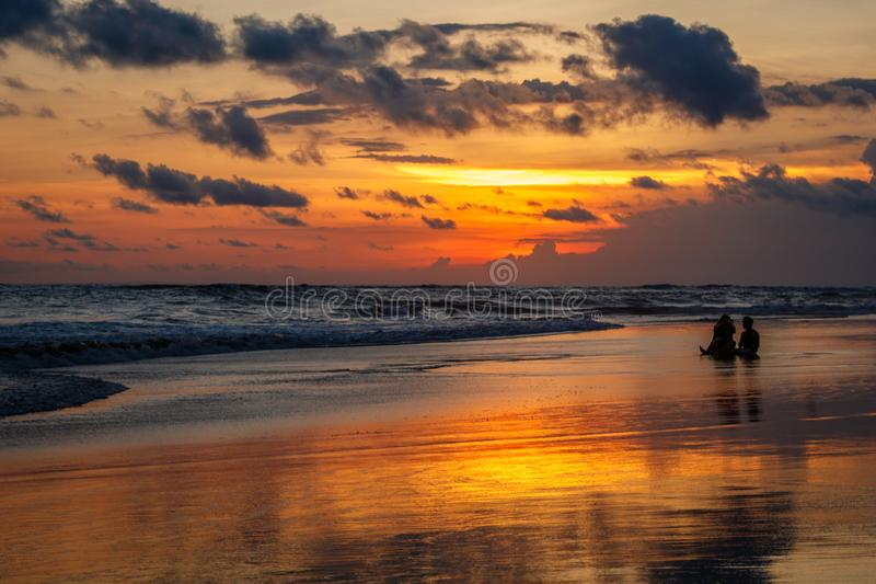 Berawa海滩在日落的Pantai Berawa 坐在浪潮的两个人剪影  Canggu,巴厘岛,印度尼西亚 库存照片