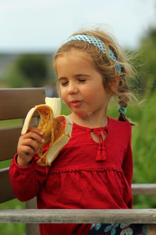 Berbeć caucasian dziewczyna cieszy się łasowanie banana plenerowego zdjęcia stock