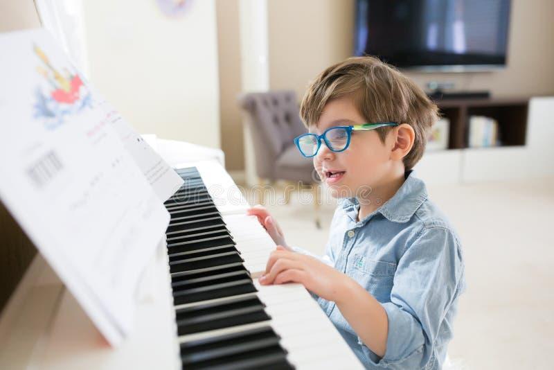 Berbeć chłopiec koncentruje na fortepianowych i muzykalnych notatkach zdjęcie royalty free