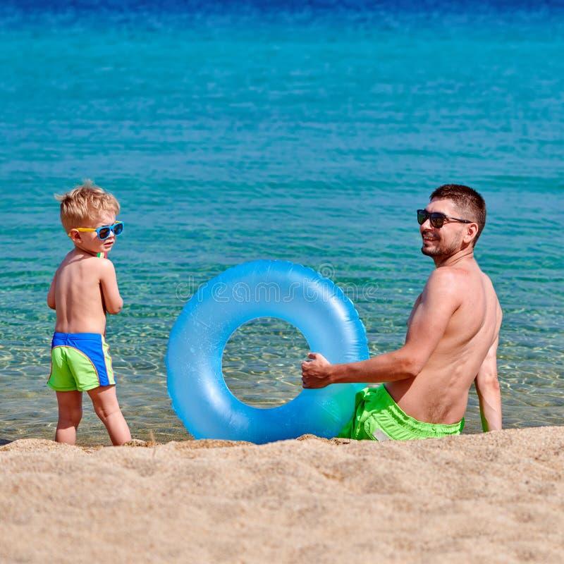 Berbeć chłopiec na plaży z ojcem fotografia stock