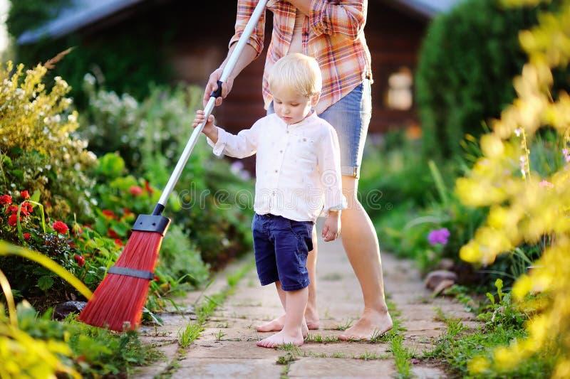 Berbeć chłopiec pomaga czystemu footpath zdjęcia royalty free