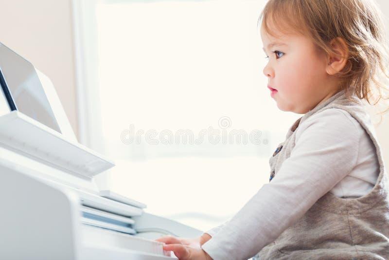 Berbeć dziewczyna bawić się pianino z pomocą od jej pastylki obraz royalty free