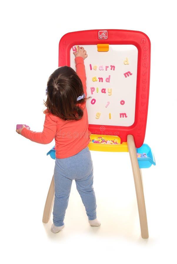 Berbeć dziewczyna bawić się z magnes deską zdjęcie royalty free