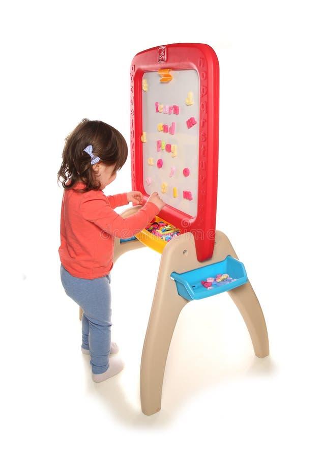 Berbeć dziewczyna bawić się z magnes deską obraz royalty free