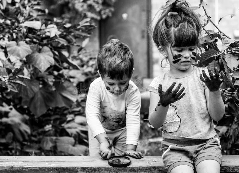 Berbeć dziewczyna i chłopiec - brudzi od bawić się w błocie zdjęcia stock