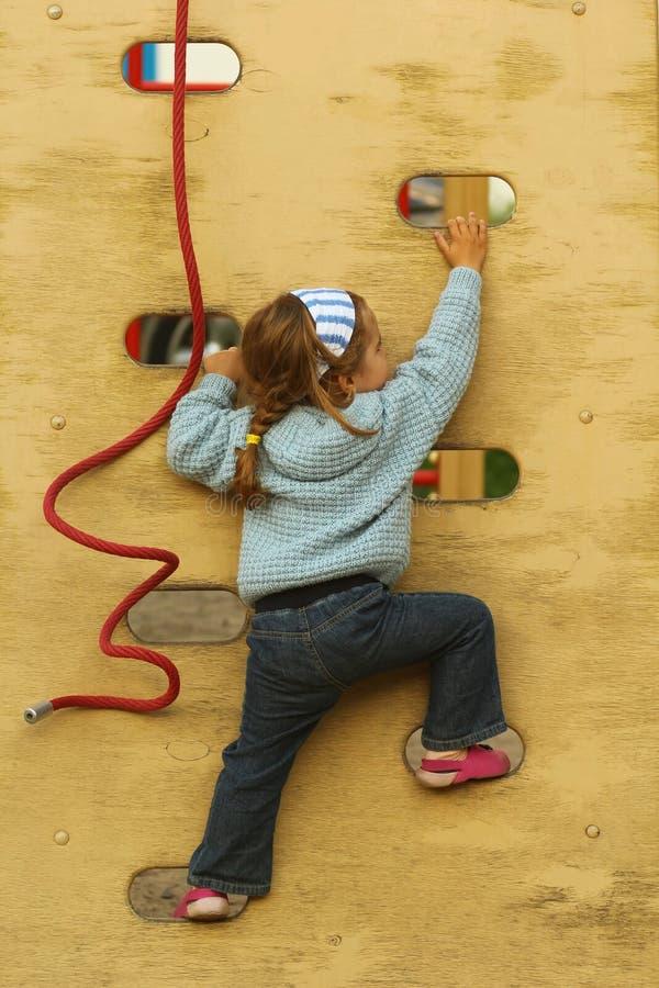 Berbeć dziewczyna wspina się ścianę na boisku w bandanach i ręcznie robiony trykotowym kardiganie obrazy stock