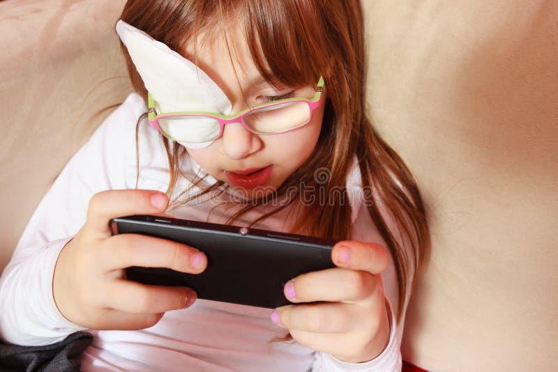 Berbeć dziewczyna z bandażem na oku bawić się gry fotografia stock