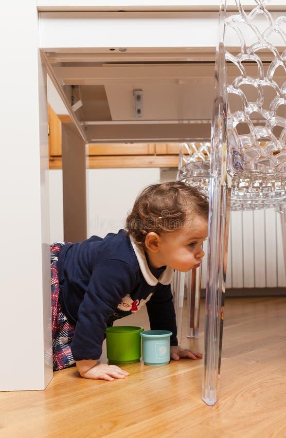 Berbeć dziewczynka bawić się pod stołem zdjęcie stock