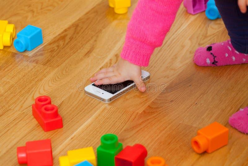 Berbeć dziewczynka bawić się z mądrze telefonem między zabawkami zdjęcie royalty free