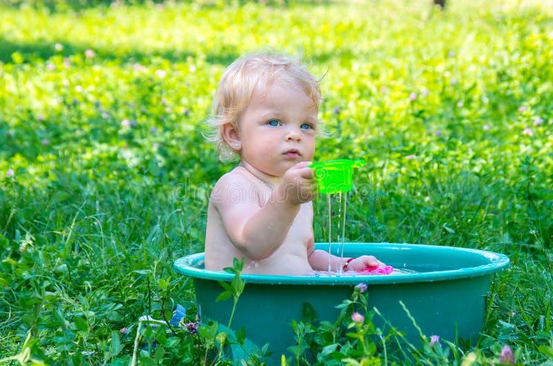Berbeć dziewczynka z niebieskimi oczami ma zabawę z wodą obraz stock