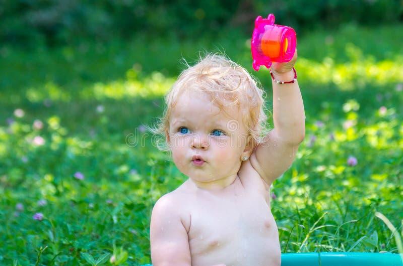 Berbeć dziewczynka z niebieskimi oczami ma zabawę z wodą fotografia stock