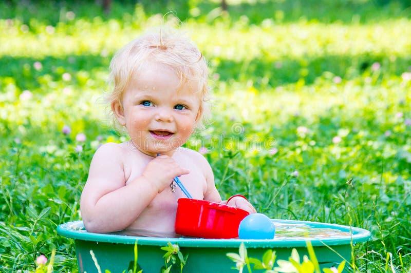 Berbeć dziewczynka z niebieskimi oczami ma zabawę z wodą w s zdjęcie royalty free