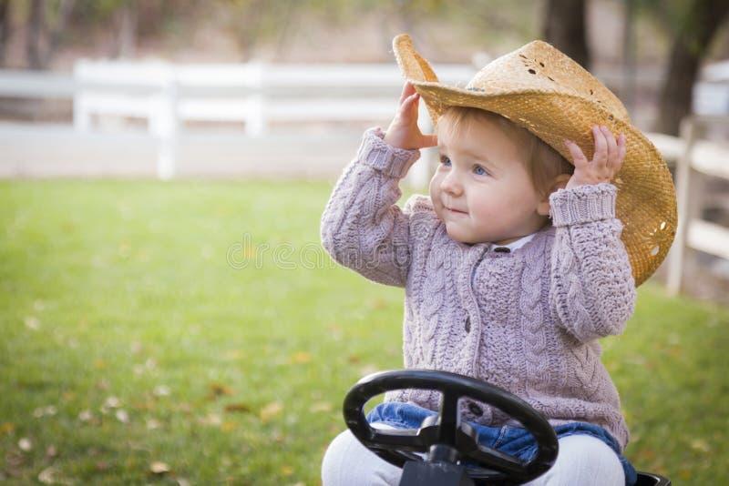 Berbeć Jest ubranym kowbojskiego kapelusz i Bawić się na Zabawkarskim Ciągnikowym Outside fotografia royalty free