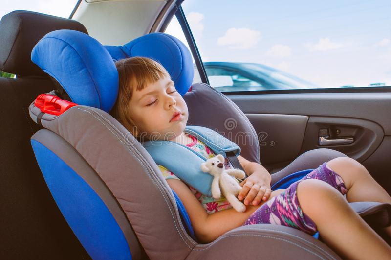 Berbeć małej dziewczynki dosypianie w samochodowym siedzeniu fotografia stock
