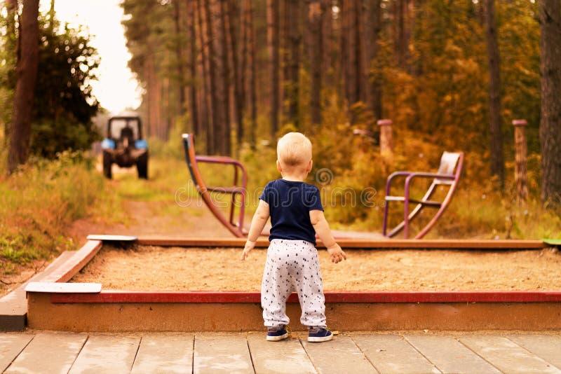 Berbeć patrzeje zamazanego ciągnika na dziecka boisku Jesieni brzmienie obraz royalty free