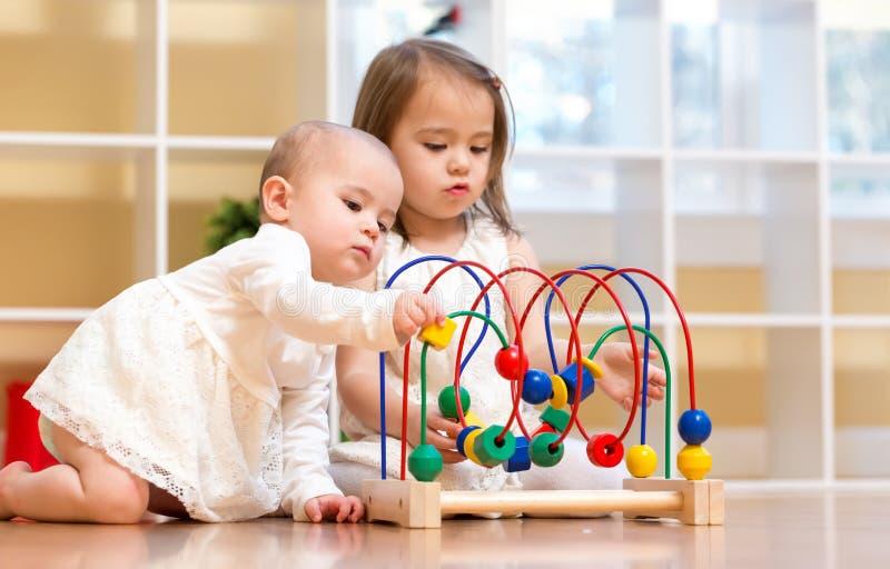 Berbeć siostry bawić się z zabawkami wpólnie zdjęcie stock