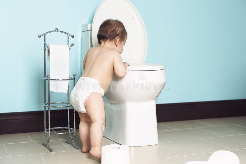 Berbeć w łazienki spojrzeniu przy toaletą zdjęcie stock