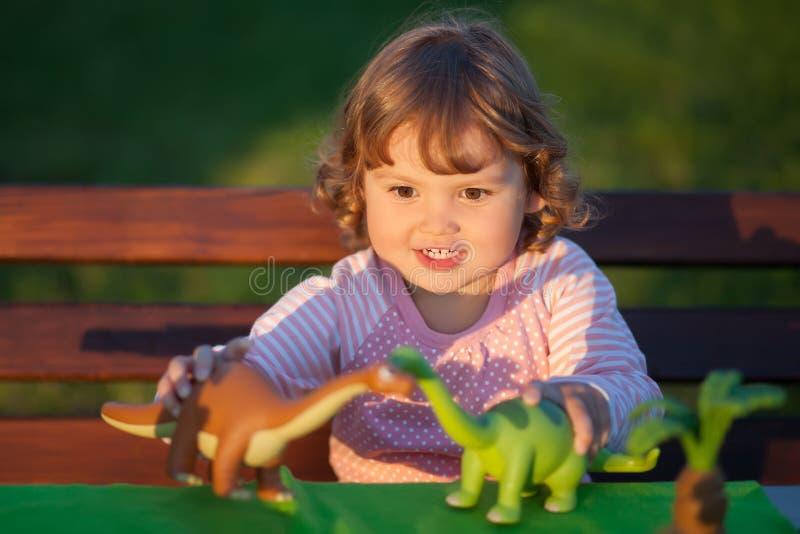 Berbecia dzieciak bawić się z zabawkarskim dinosaurem zdjęcie royalty free