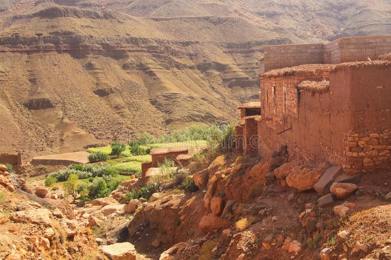 Berber village in valley surrounded by rugged high mountain walls with old brick clay houses royalty free stock images
