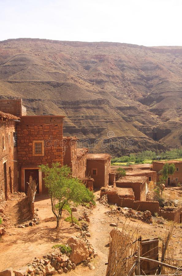 Berber village in valley surrounded by rugged high mountain walls with old brick clay houses stock images