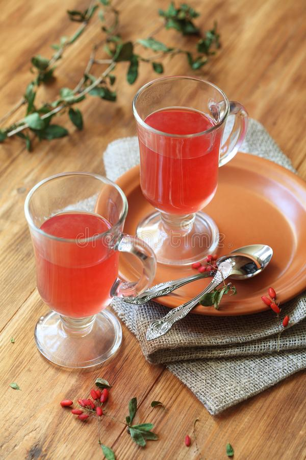 Berberis tea. Two cups of hot berberis tea, on wooden background stock image