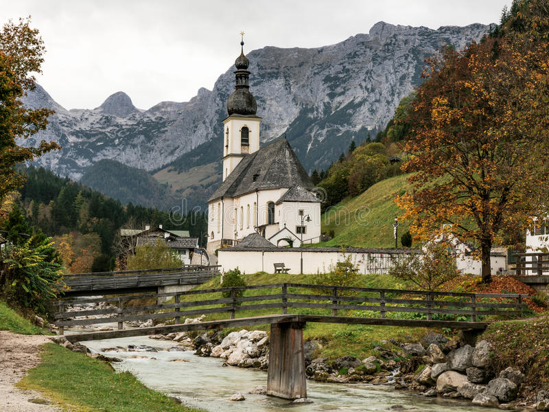 Berchtesgaden Church. White Church in front of the Mountains of Berchtesgaden on a small creek with a bridge in Germany. Autumn Landscape Picture from Bavaria stock photo